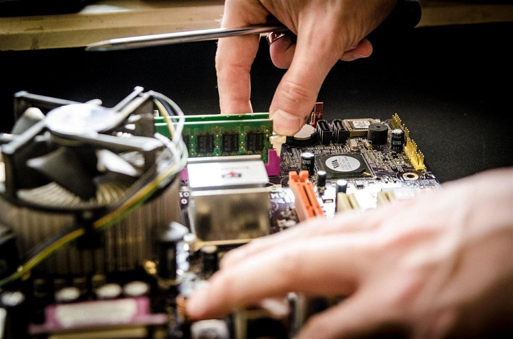 Eine Person repariert eine Kühlschrank-Platine